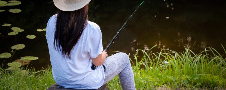 Young woman fishing in pond in summer evening